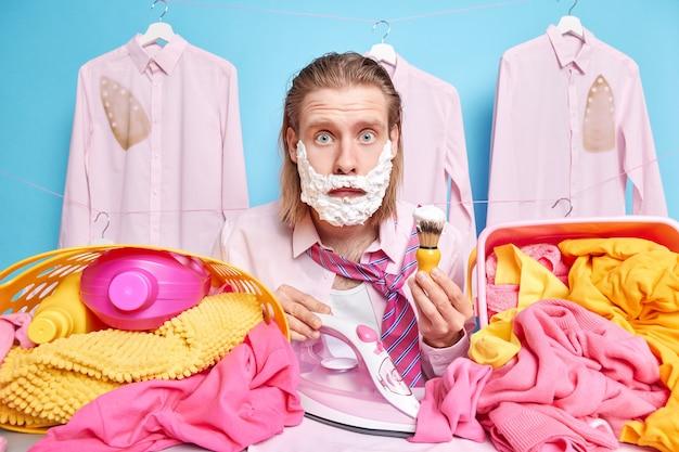 남자가 작업 준비를 마치고 넥타이 면도와 다리미로 비즈니스 셔츠를 입고 다림질 보드 드레스 근처에서 충격을받은 세탁 포즈는 빨리 늦게 깨어납니다.