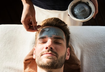 Man getting a mud mask at a spa