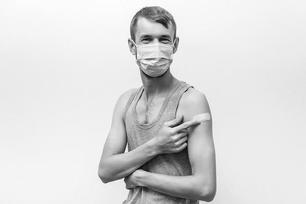 コロナワクチン接種を受けている男性。フェイスマスクを着用している人。ワクチン接種後、包帯で腕を見せて幸せな男。