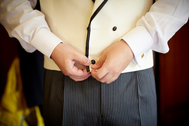 Man getting dressed. buttoning up his vest