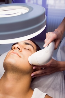 Man getting a facial massage at clinic