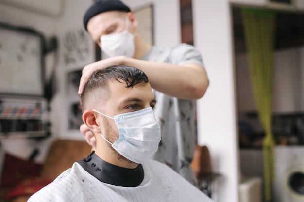 コロナウイルスのパンデミック中にマスクを着用して理髪店で髪を切っている男性。手袋をはめたプロの床屋。 covid-19、美容、セルフケア、スタイル、ヘルスケア、医学のコンセプト。