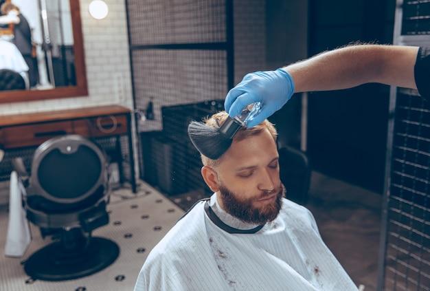코로나바이러스 전염병 동안 마스크를 쓰고 이발소에서 머리를 자르는 남자. 장갑을 끼고 전문 이발사. 코비드-19, 아름다움, 자기 관리, 스타일, 건강 관리 및 의학 개념.