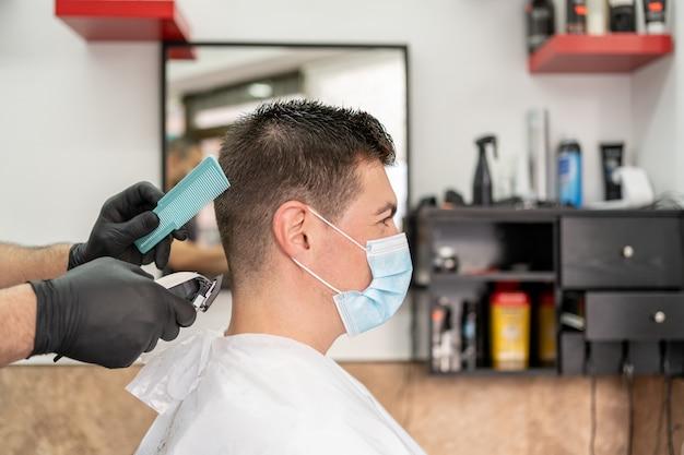 이발소 착용 마스크에서 머리를 잘라 남자.