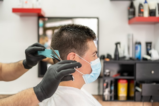 Man getting hair cut at the barbershop wearing mask.