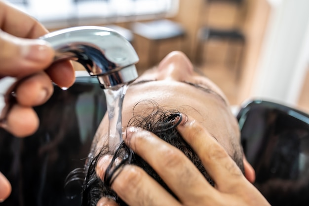 Man getting a hair washed in barber shop.