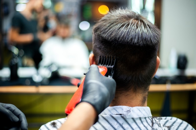 Man getting a haircut with blurred mirror reflection