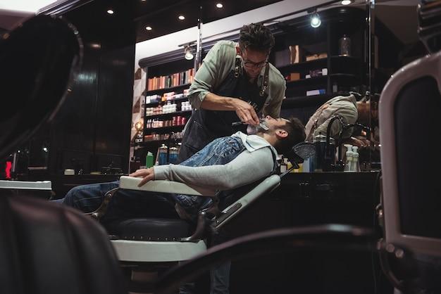 Мужчина бреет бороду бритвой