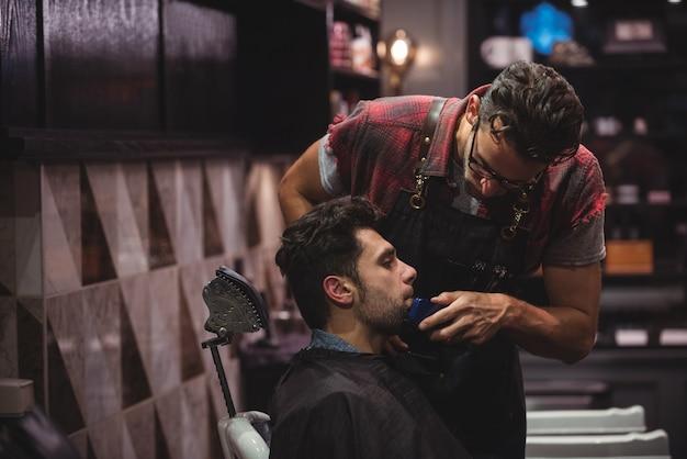 Uomo che ottiene la sua barba rasata con il rifinitore