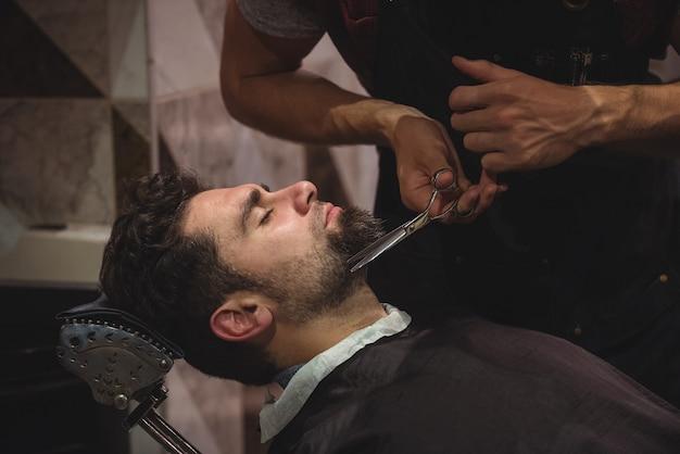 はさみで髭を整える男