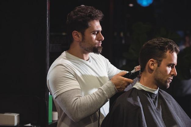 Uomo che ottiene i suoi capelli tagliati con trimmer