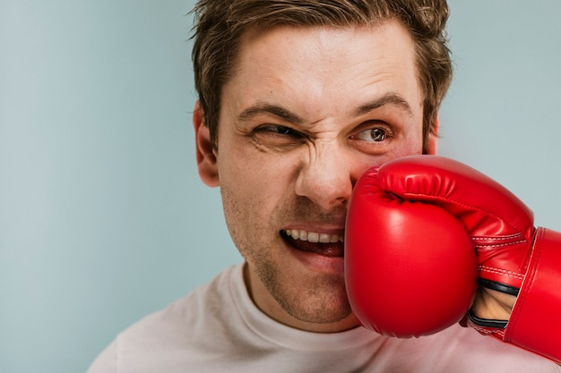 赤いボクシンググローブで殴られる男