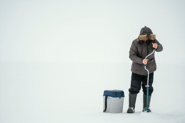 얼어 붙은 호수에서 낚시를 준비하는 남자