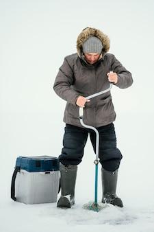凍った湖で釣りの準備をしている男