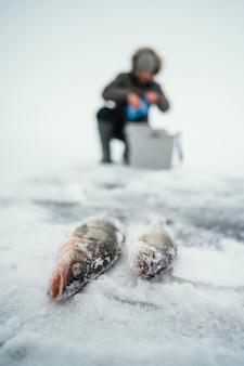 얼어 붙은 호수에서 낚시를 준비하는 남자 무료 사진