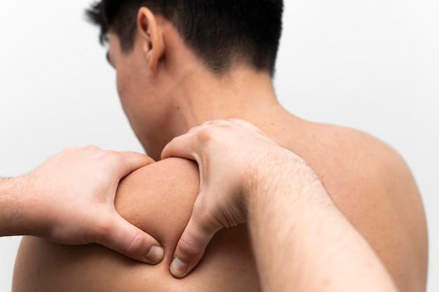 理学療法士から痛みのために肩のマッサージを受けている男性