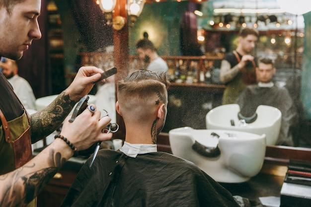 이발소에서 트렌디한 머리를 하고 있는 남자. 고객에게 봉사하는 문신의 남성 미용사.