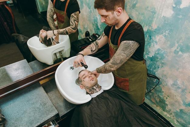 Uomo che ottiene taglio di capelli alla moda al negozio di barbiere. l'hairstylist maschile in tatuaggi che serve il cliente, lavando la testa