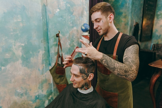 Man getting trendy haircut at barber shop. the male hairstylist in tattoos serving client.