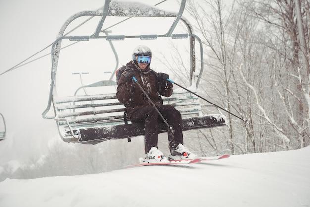 スキーリフトから起き上がる男