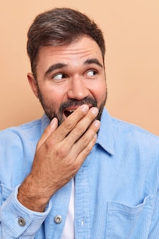 Man giggles and cons mouth with hand tries to hide his emotions laughs at something funny wears blue velvet shirt isolated on beige