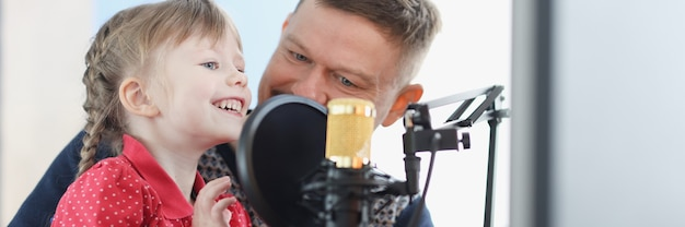 Man and girl are recording their voice on microphone music lessons for adults and children