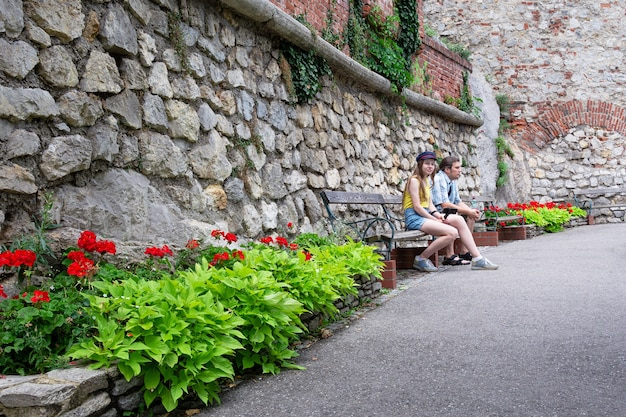 A man and a girl are sitting on a bench in the park against a stone wall.