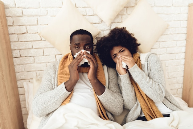 Man and girl in bed blow their nose.