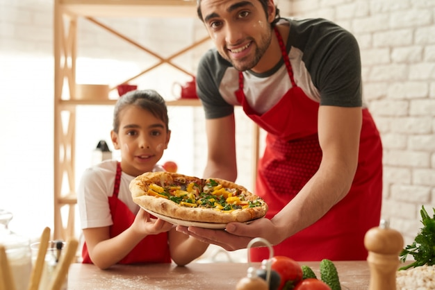Man and girl cooked beautiful pizza on kitchen.