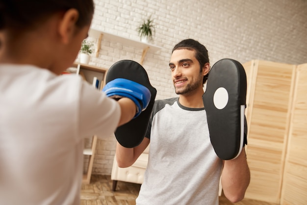 Man and girl have boxing training at home.