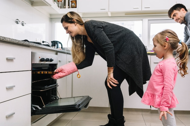 Man and girl looking at woman baking cookies in oven