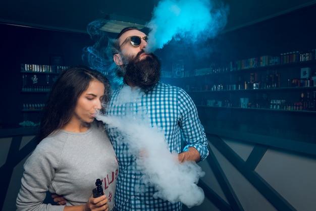 A man and a girl smoke a cigarette and release smoke.