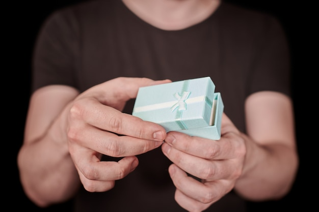 Человек дает подарок в подарочной коробке. открытие подарка ко дню святого валентина. маленькая юбилейная подарочная коробка от мужчины. маленькая концепция-сюрприз. черный фон.