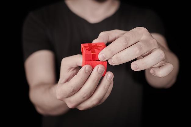 Человек дает подарок в красной подарочной коробке. открытие подарка ко дню святого валентина. маленькая юбилейная подарочная коробка от мужчины. маленькая концепция-сюрприз. черный фон.