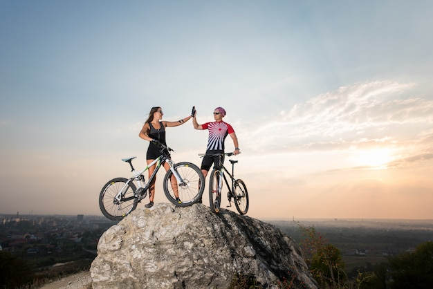 Man give high five for woman on rock