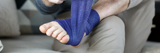 Man give himself first aid rolling blue bandage tape over foot close-up