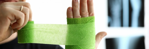 Man give himself first aid rolling green bandage tape over wrist close-up