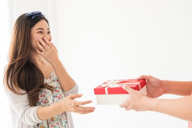 남자는 흰색 배경에 고립 된 그의 아름 다운 아시아 여자에게 빨간색 선물 상자에 깜짝 선물을 제공합니다.