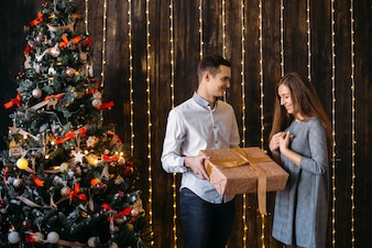 Man gives a present to the woman standing before a Christmas tree