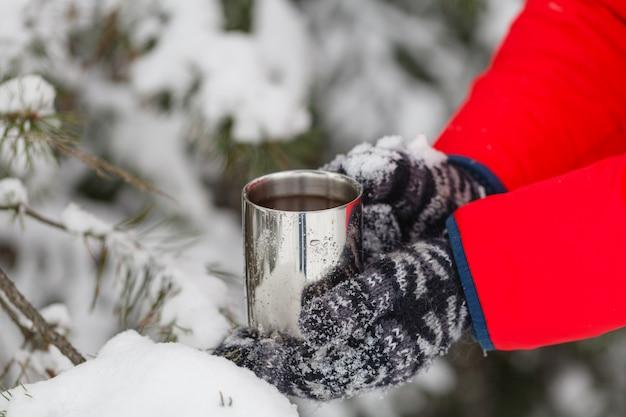男は屋外で居心地の良い雪に覆われた冬の朝を楽しんで、熱いお茶やコーヒーのカップを与える