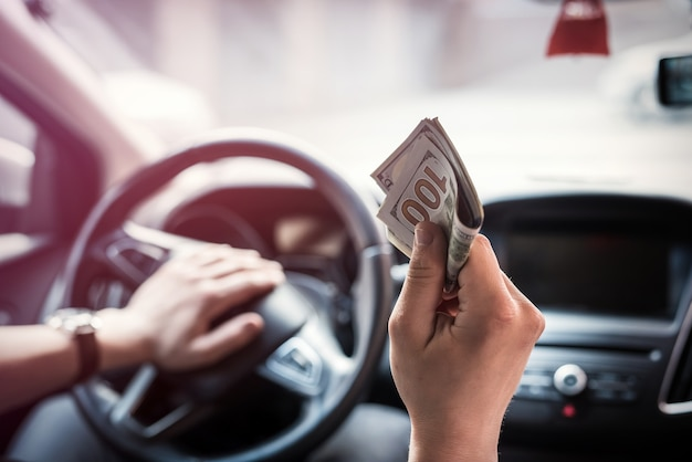 Man gives dollars while sitting in the car. concept of shopping, money
