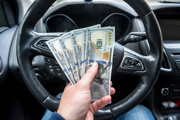 男は車に座っている間ドルを与えます。ショッピング、お金の概念