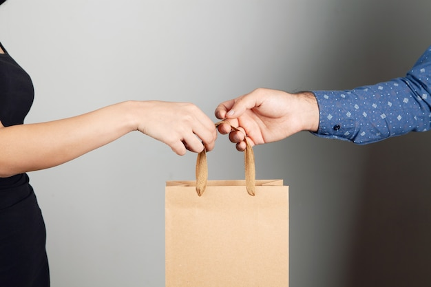 Мужчина дает подарочный пакет женщине на сером фоне
