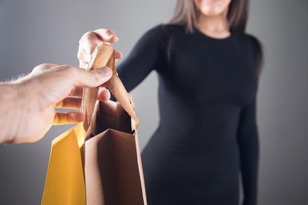 남자는 회색 배경에 여자에게 선물 가방을 준다