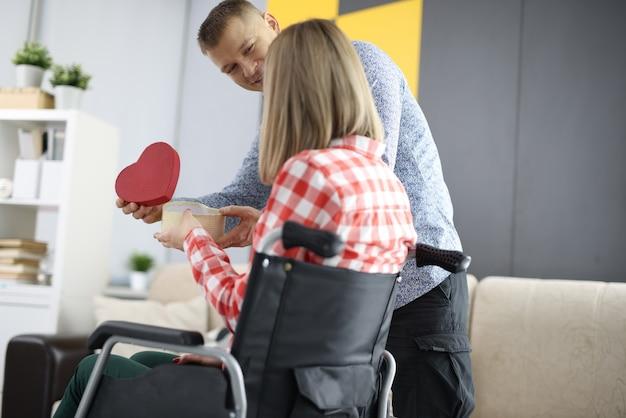Man gives gift to woman in wheelchair. relationship with disabled person concept