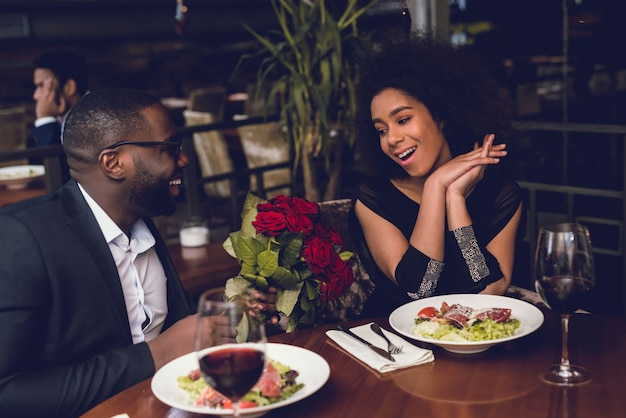 Man gives his girlfriend beautiful flowers in a restaurant.