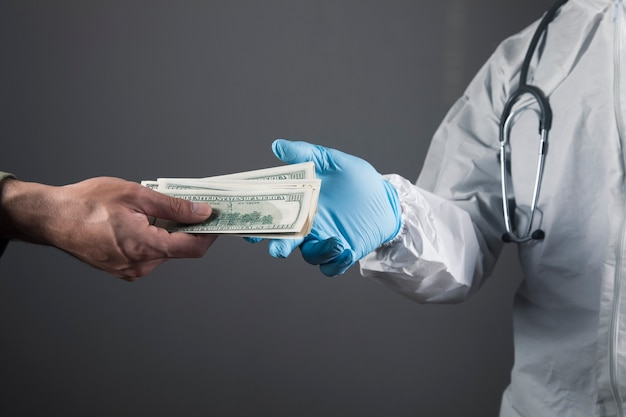 A man gives money to a doctor on a gray scene