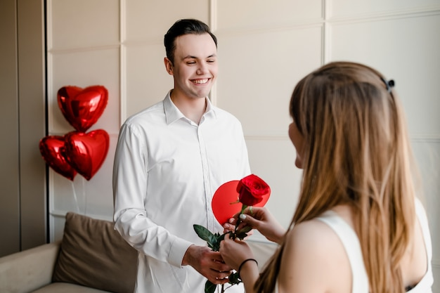 Man gives rose with a gift to woman at home with heart shaped red balloons