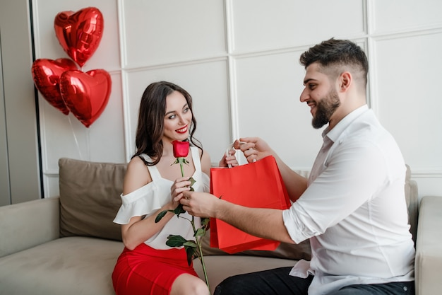 Man gives shopping bags and red rose to woman at home with heart shaped balloons on couch