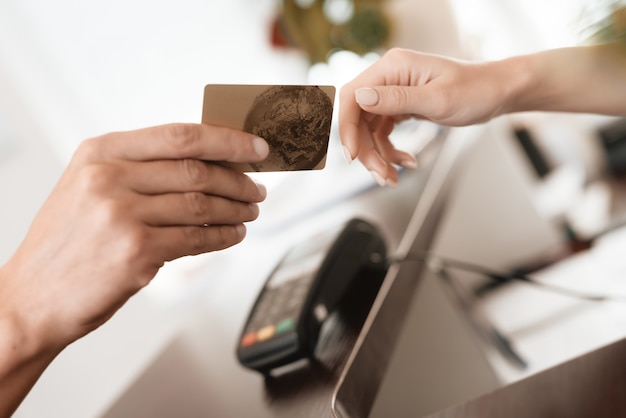 A man gives a woman a bank card for payment.